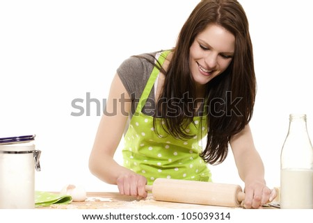 happy young woman using rolling pin on dough with white background - stock photo