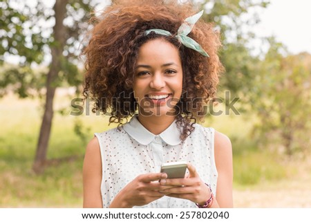 Happy young woman using smartphone on a sunny day - stock photo