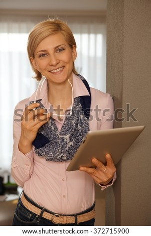 Happy young woman using tablet computer, smiling, looking at camera. - stock photo