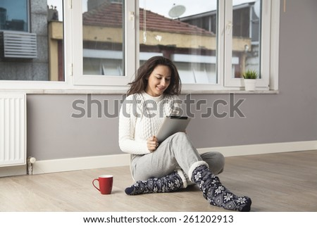Happy young woman using the tablet computer while sitting on the floor at home.