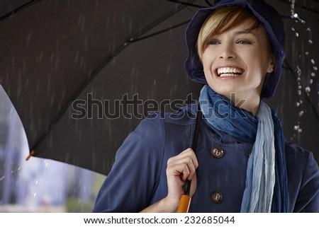 Happy young woman using umbrella in rain, smiling. - stock photo