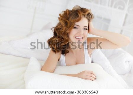 happy young woman waking up in white bed in morning. Smiling emotional portrait. young beautiful girl in bed. Sensual woman lwith white pillow. cute lovely young woman with curly red hair lying in bed