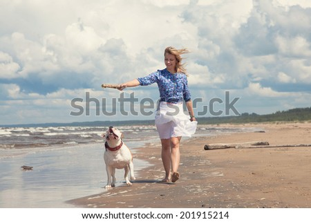happy young woman walking with dog - stock photo