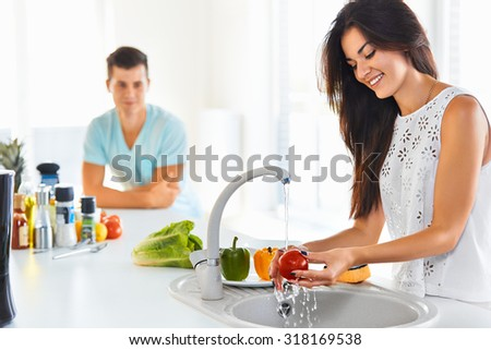 Happy young woman washing vegetables in the sink and handsome man standing next to her. Focus on the girl. - stock photo