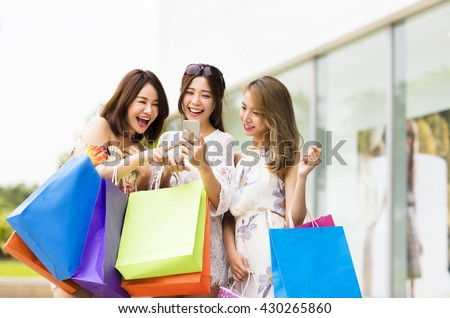 happy young woman  watching smart phone in shopping mall - stock photo