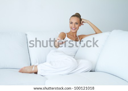 Happy young woman watching tv on sofa - stock photo