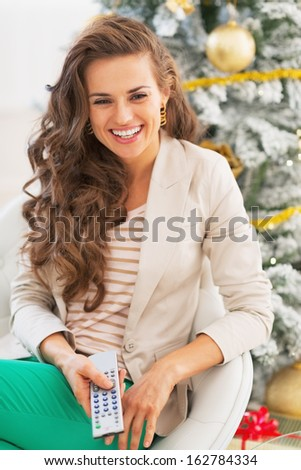 Happy young woman watching tv remote near christmas tree  - stock photo