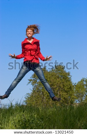 Happy Young woman wearign jeans and red coat jumping in the sky