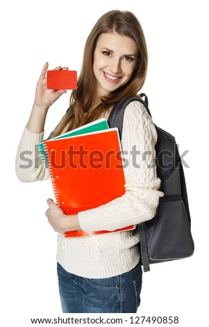 Happy young woman wearing a backpack and holding notebooks showing blank credit card, over white background. Student loan concept.