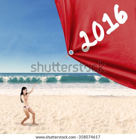 Happy young woman wearing bikini on the beach and pulling numbers 2016 with a big flag