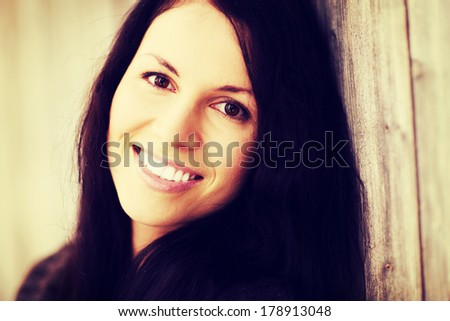 Happy young woman wearing brown cardigan is smiling, outside in winter day. Pretty woman with long hair.