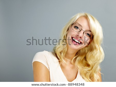 Happy young woman wearing eyeglasses on grey background