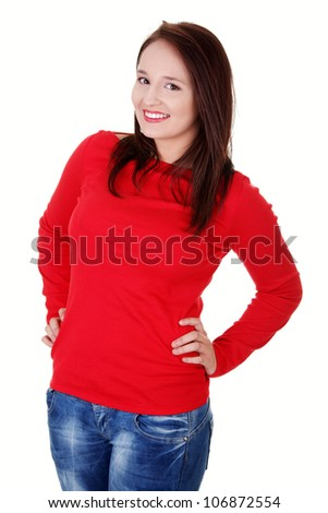 Happy young woman wearing red blouse and jeans is standing and smiling with hands on hips. Isolated on white background.