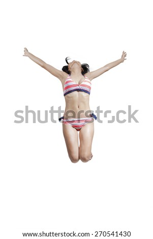 Happy young woman wearing swimwear and jumping in the studio to enjoy her freedom - stock photo