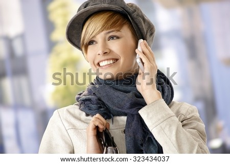 Happy young woman wearing winter clothes talking on mobile, outdoors.
