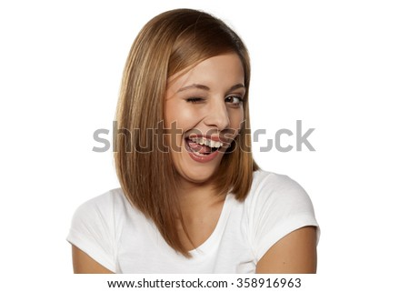happy young woman winking on a white background