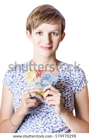Happy young woman with a beaming smile holding Australian money in hand celebratng a payout or bonus - stock photo