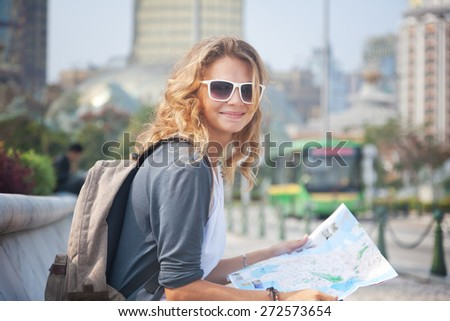 happy young woman with a city map and a backpack smiling - stock photo