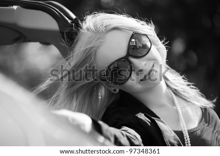 Happy young woman with a convertible car - stock photo
