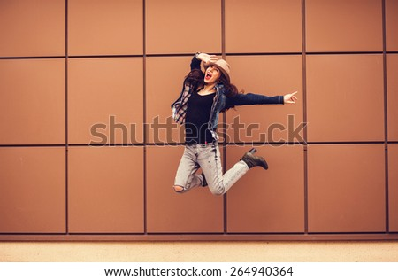 happy young woman with a hat jumping near the wall. freedom - stock photo