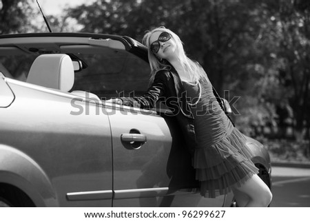 Happy young woman with a new car - stock photo