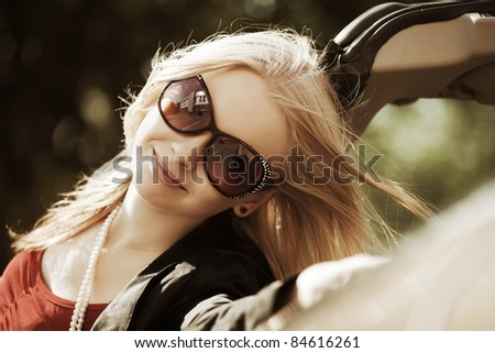 Happy young woman with a new convertible car - stock photo