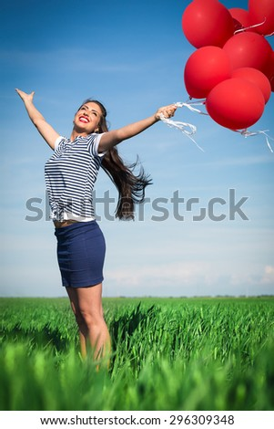 Happy young woman with a red balloon on a green meadow - stock photo