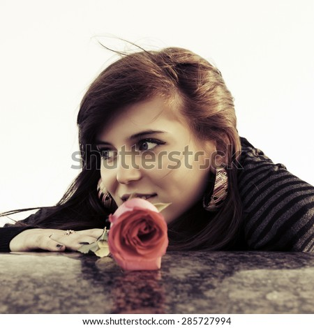 Happy young woman with a red rose outdoor - stock photo