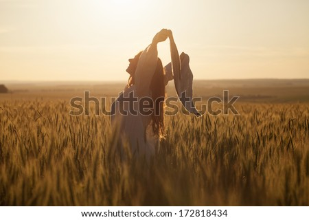 Happy young woman with a shawl in field - stock photo