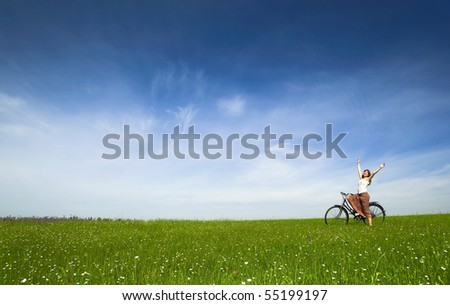 Happy young woman with a vintage bicycle on a green meadow - stock photo