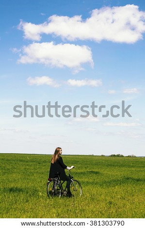 Happy young woman with a vintage bicycle on a green meadow. Young woman really anoyed beacuse of her to broken bicycle. beautiful girl on a vintage bike