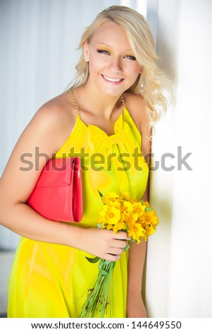 Happy young woman with a yellow bunch of flowers