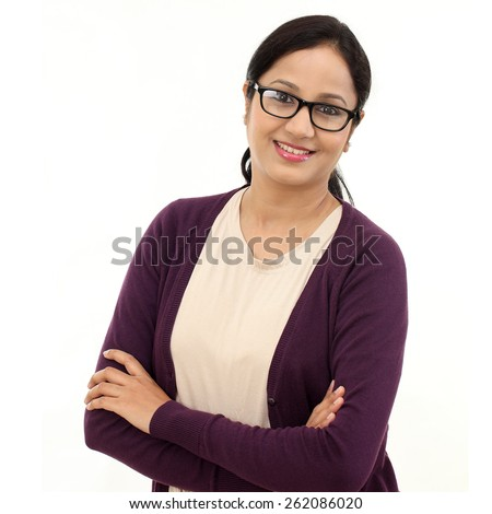 Happy young woman with arms crossed against white - stock photo
