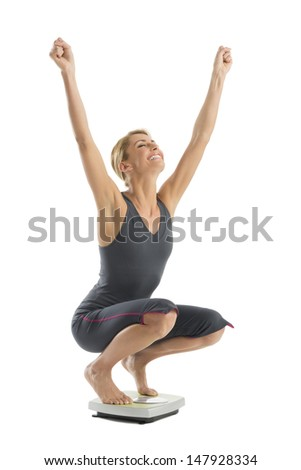 Happy young woman with arms raised crouching on weight scale isolated over white background - stock photo