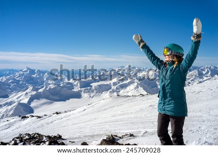 Happy young woman with arms raised on background of the snowy high mountains and beautiful landscape - stock photo