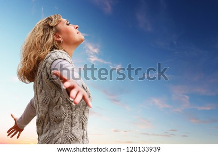 Happy young woman with arms raised towards a blue sky