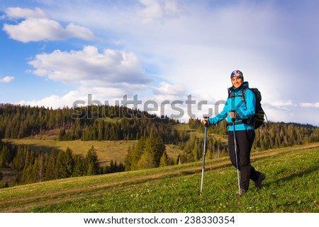 Happy young woman with backpack and trekking sticks hiking in the mountayns against the blue sky with beautiful clouds.