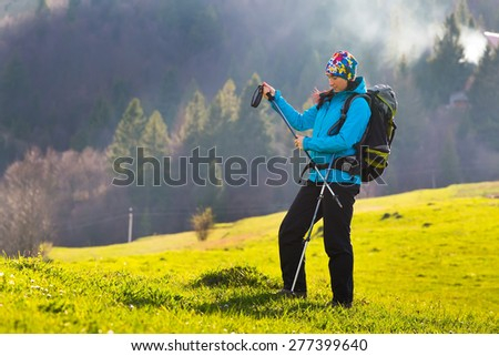 Happy young woman with backpack and trekking sticks hiking in the mountayns against the blue sky with beautiful clouds. - stock photo