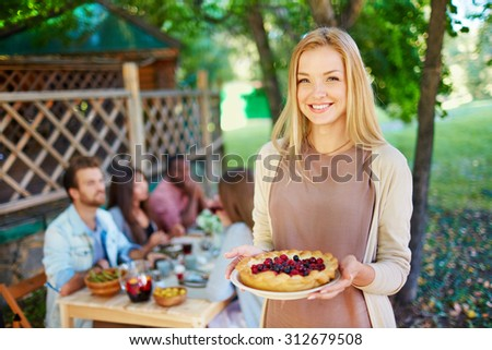 Happy young woman with berry pie looking at camera on background of her friends sitting by Thanksgiving table