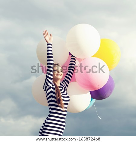 Happy young woman  with big colorful latex balloons. Girl waving to someone. Outdoors, lifestyle - stock photo