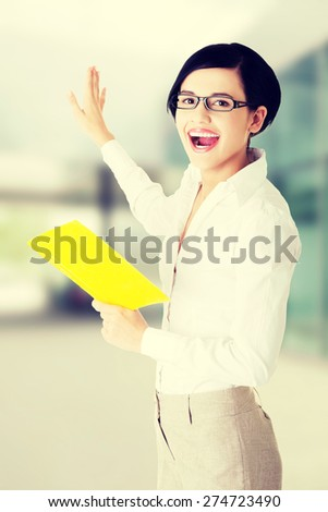 Happy young woman with book in hand showing on copy space - stock photo