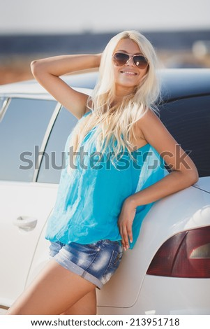 happy young woman with car - sexy rich lady driver with long blond healthy hair at automobile . spring - summer portrait . beautiful slim fashion girl posing near car - stock photo