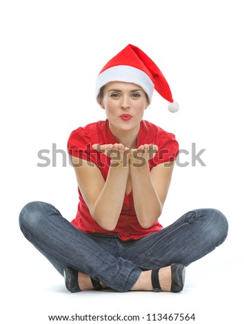 Happy young woman with Christmas hat sitting on floor and blowing kiss - stock photo
