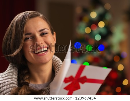 Happy young woman with Christmas postcard - stock photo
