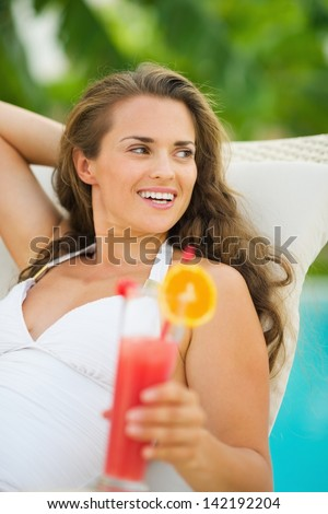 Happy young woman with cocktail laying on chaise-longue - stock photo