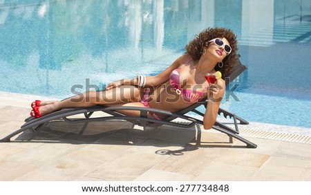 Happy young woman with cocktail on deck chair and enjoying sun - stock photo
