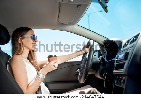 Happy young woman with coffee to go driving her car - stock photo