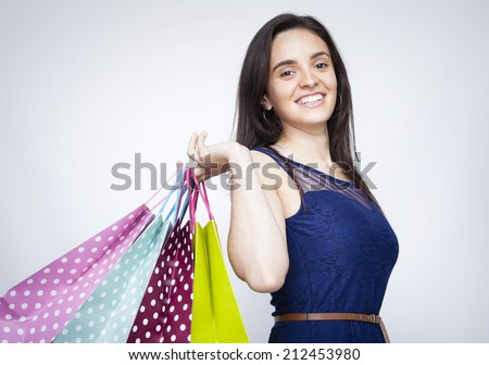 Happy young woman with colored shopping bags over gray background