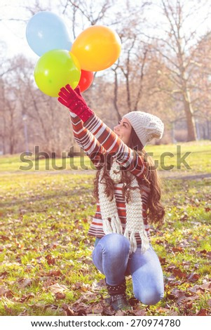 Happy Young Woman With Colorful Balloons at beautiful sunny autumn day. Carefree Female lifestyle scene.