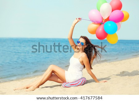 Happy young woman with colorful balloons on beach near sea enjoys summer day - stock photo